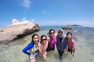 wisatawan berfoto di pulau batu berlayar